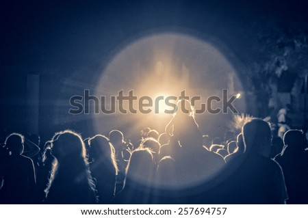 crowd at a concert in a vintage light, noise added - stock photo