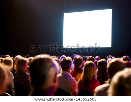 Crowd audience in dark looking at bright screen - stock photo