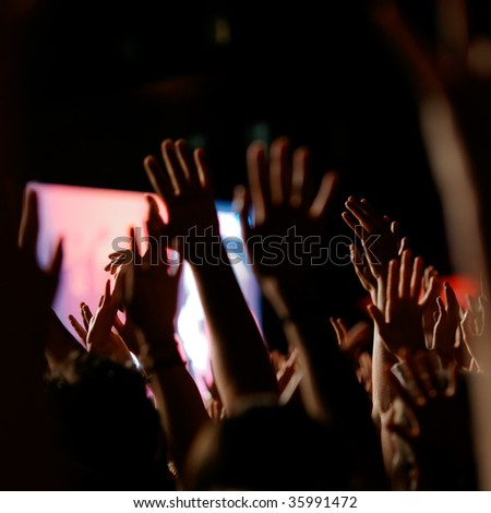 Crowd cheering at a concert. Back-lit. - stock photo