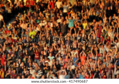 Crowd in a stadium. Blurred heads and faces of spectators - stock photo