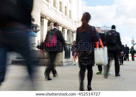 crowd of commuters walking on the London Bridge in London, UK, in motion blur - stock photo