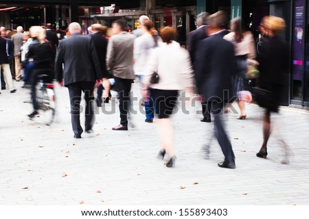 crowd of dressed up people in motion blur walking to a concert - stock photo