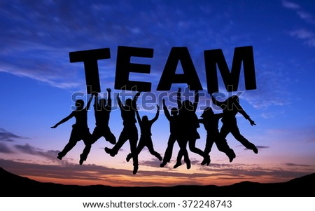 """Crowd of friends jumping with """"TEAM"""" on blue sky background - stock photo"""