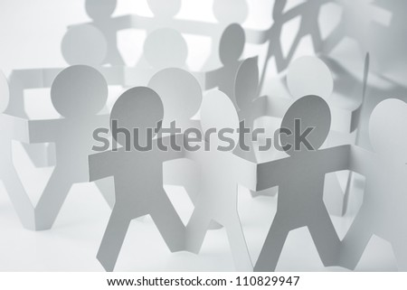 Crowd of paper chain people holding hands - stock photo
