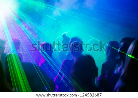 Crowd of people dancing under disco laser light. - stock photo