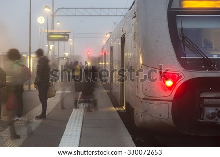 Crowd of people getting on and off train on foggy day - stock photo