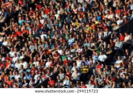 Crowd of people in a stadium - blurred image - stock photo