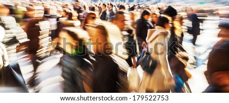 crowd of people walking on a city square in motion blur and zoom effect - stock photo