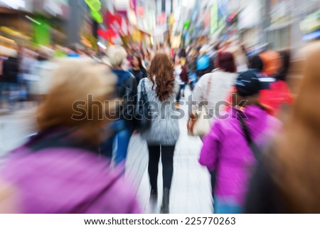 crowd of shopping people in the city with creative zoom effect, made by camera - stock photo