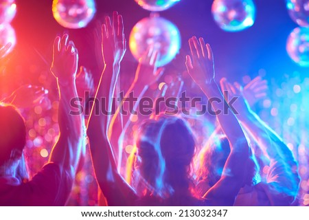 Crowd of young people dancing in night club - stock photo
