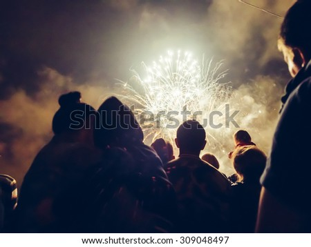 Crowd watching fireworks and celebrating - stock photo