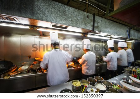 Crowded kitchen, a narrow aisle, working chef. - stock photo