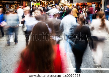 crowds of people crossing the street in the city in motion blur - stock photo