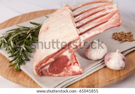 crown of lamb with rosemary and garlic or rack of lamb. gourmet dinner ready to be cook. raw meat from sheep - stock photo
