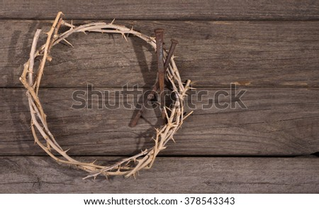 Crown of thorns and nails on a rustic wood surface - stock photo