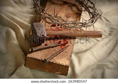 Crown of thorns, nails and hammer on wooden cross - stock photo