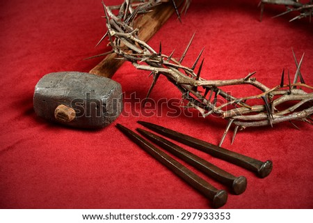 Crown of thorns, nails and hammer representing crucifixion symbols on red cloth - stock photo