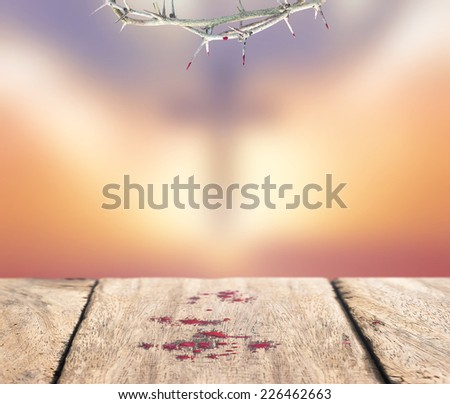 Crown of thorns with blood and drops of blood on old wooden floor over blurred the cross on a sunset. - stock photo