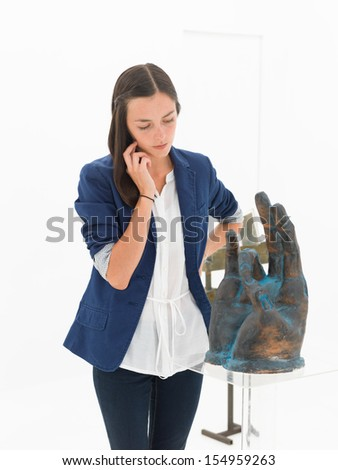 crpped view of woman thinking about the message behing the artwok standing in front of her - stock photo