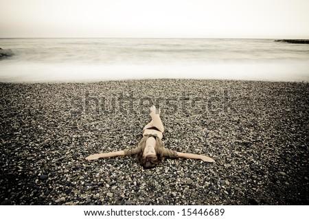 Crucified woman in stone beach, long exposure - stock photo