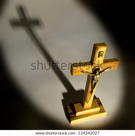 Crucifix with spotlight lighting casting shadow - stock photo