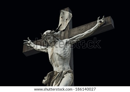 Crucifixion. Christian cross with Jesus Christ statue isolated on black background with clipping work path. Religion and spirituality concept. - stock photo