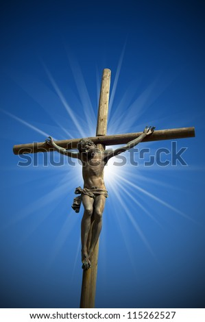 Crucifixion - The Jesus on the Cross / The cross (bronze and wood) - symbol of God's on blue sky - stock photo