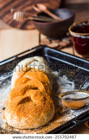 Crude bun with cinnamon during cooking, butter raw dough, sweet pastries - stock photo