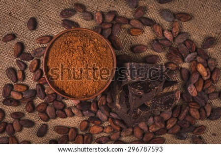 crude dark cocoa powder in a brown ceramic bowl, raw cocoa beans in the peel and raw chocolate on sacking close up, top view, ingredients for preparing chocolate and sweets - stock photo