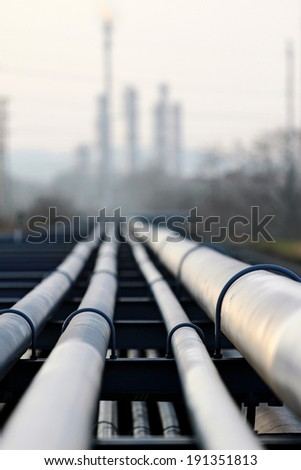 crude oil pipeline and oil  refinery against light - stock photo