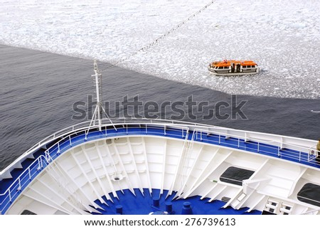 Cruise Ship bow passing icy snow arctic waters near Spitsbergen, Svalbard, Norway with lifeboat on water.  - stock photo