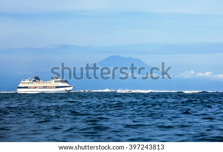 cruise ship in the sea with island - stock photo