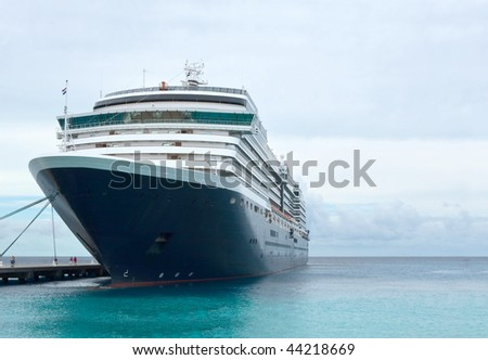 Cruise ship tied up at pier. - stock photo