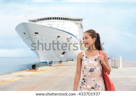 Cruise Ship Vacation Happy Female Tourist on Pier. Smiling happy young woman walking on pier by huge cruise ship moored at jetty. Beautiful woman in casuals is enjoying her vacation. - stock photo