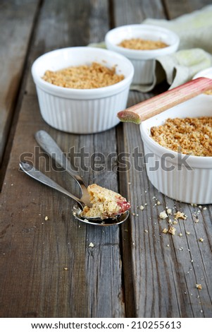 Crumble cake with rhubarb in a baking dish on a wooden background, selective focus - stock photo