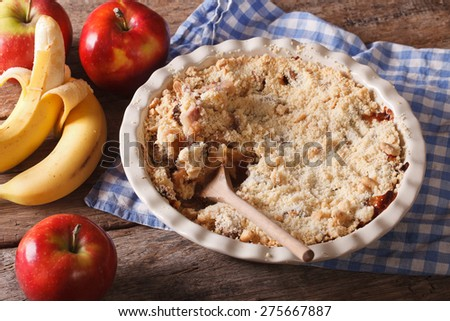 Crumble with apple and banana close-up on the table. horizontal, rustic style