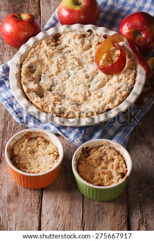 Crumble with apples close-up in baking dish. Vertical, rustic style