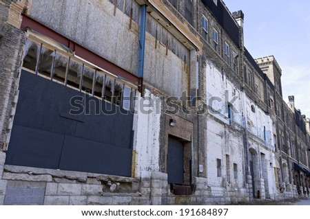 Crumbling facade of abandoned warehouse with boarded windows and broken glass in rust belt - stock photo