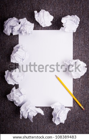 Crumpled and wrinkled white paper wads with fresh sheet of blank paper over dark texture - stock photo