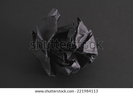 Crumpled black paper ball on a black background. - stock photo