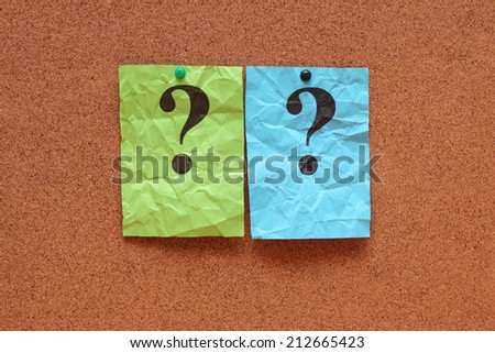 Crumpled colorful paper notes with question marks on corkboard (bulletin board). - stock photo