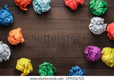 crumpled colorful paper on wooden background creative process - stock photo