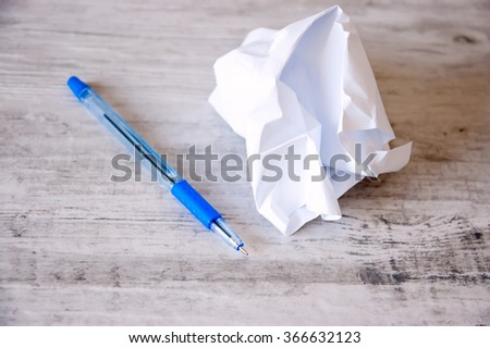crumpled paper and a pen on a retro background - stock photo