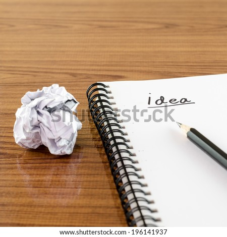 crumpled paper and pencil with notebook write idea word on wood background - stock photo