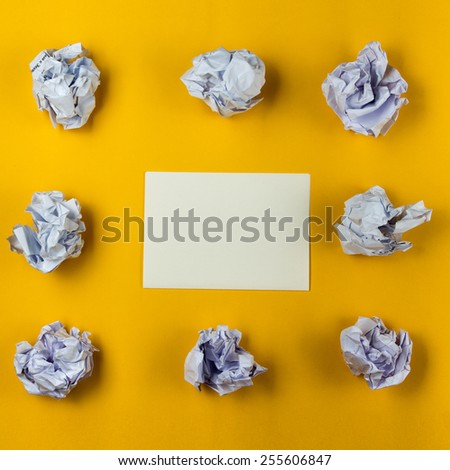 Crumpled paper balls and blank sheet of paper on yellow background. Creativity problems. Searching ideas. - stock photo