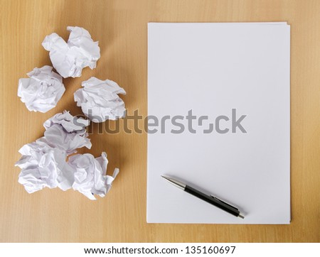 Crumpled paper balls and blank sheet of paper with pen - stock photo