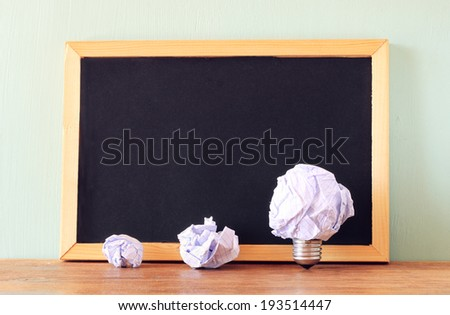 crumpled paper light bulb metaphor as idea or inspiration and empty black board - stock photo