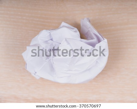 crumpled paper on a wooden background - stock photo
