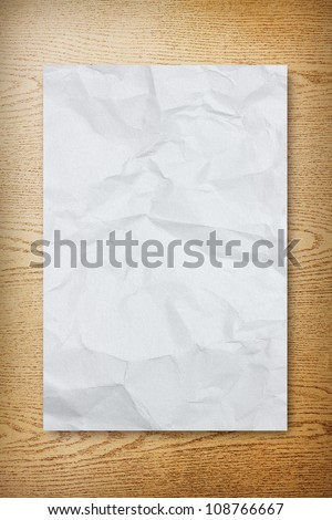 Crumpled paper on wood background - stock photo
