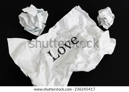Crumpled paper sheet with word Love isolated on black - stock photo
